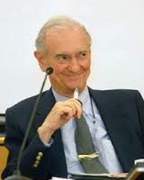 A photo of Dr. Wolf Wolfensberger sitting before a microphone with a pen in his hand.