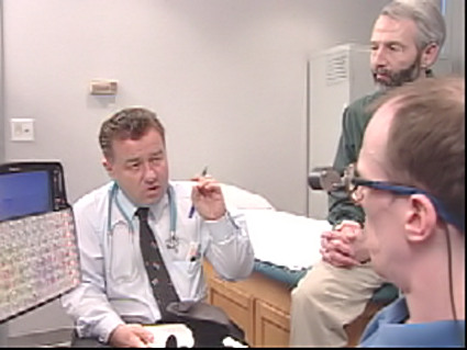 A doctor speaks with an individual with cerebral palsy and his personal care assistant.